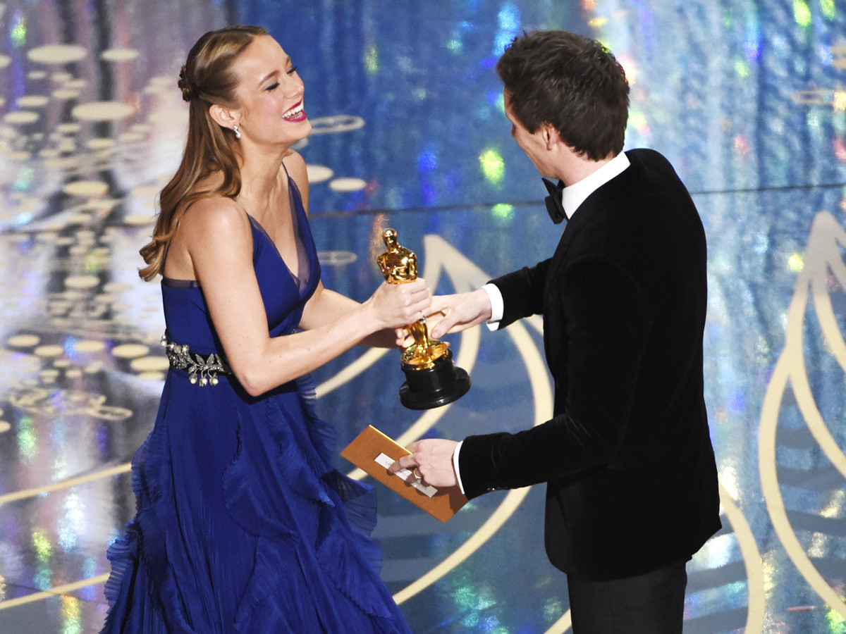 Eddie Redmayne, right, presents Brie Larson with the award for best actress