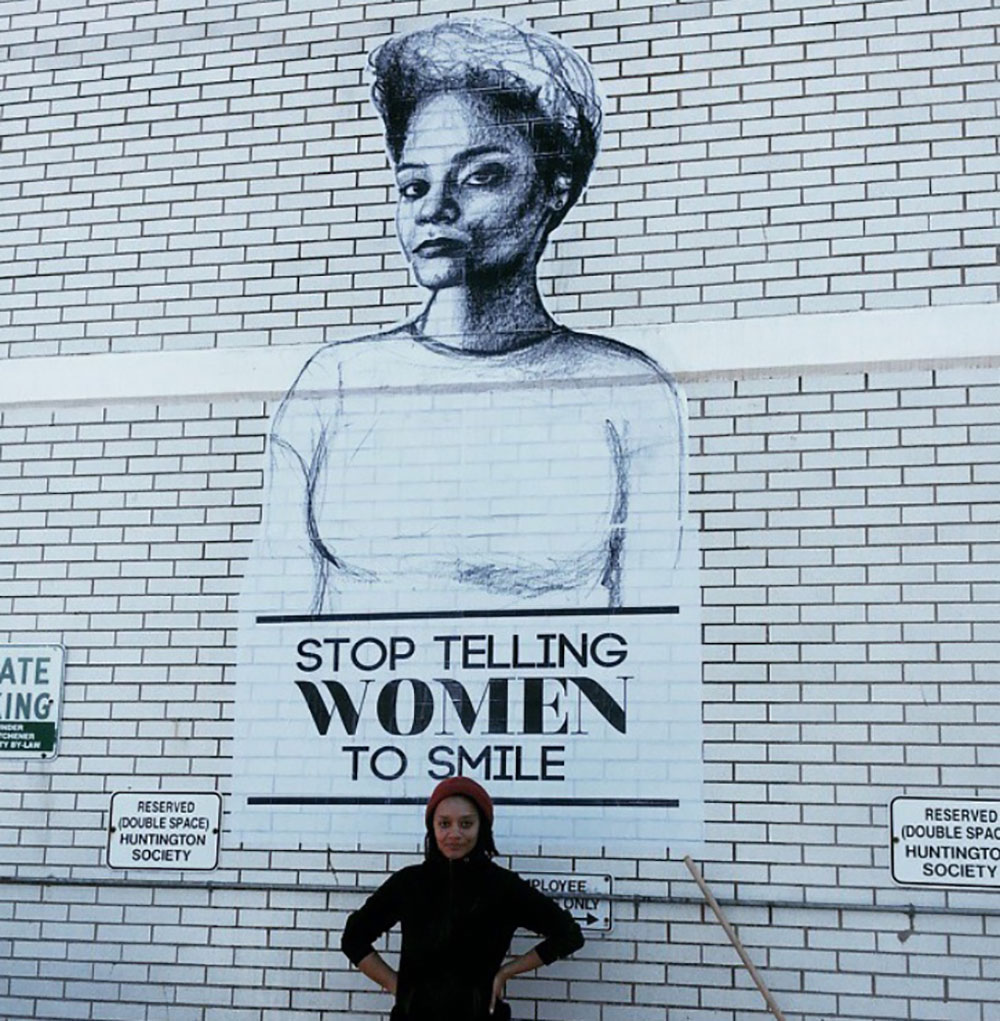 Artist Tatyana Fazlalizadeh stands in front of the posters she created as part of 'Stop Telling Women To Smile'