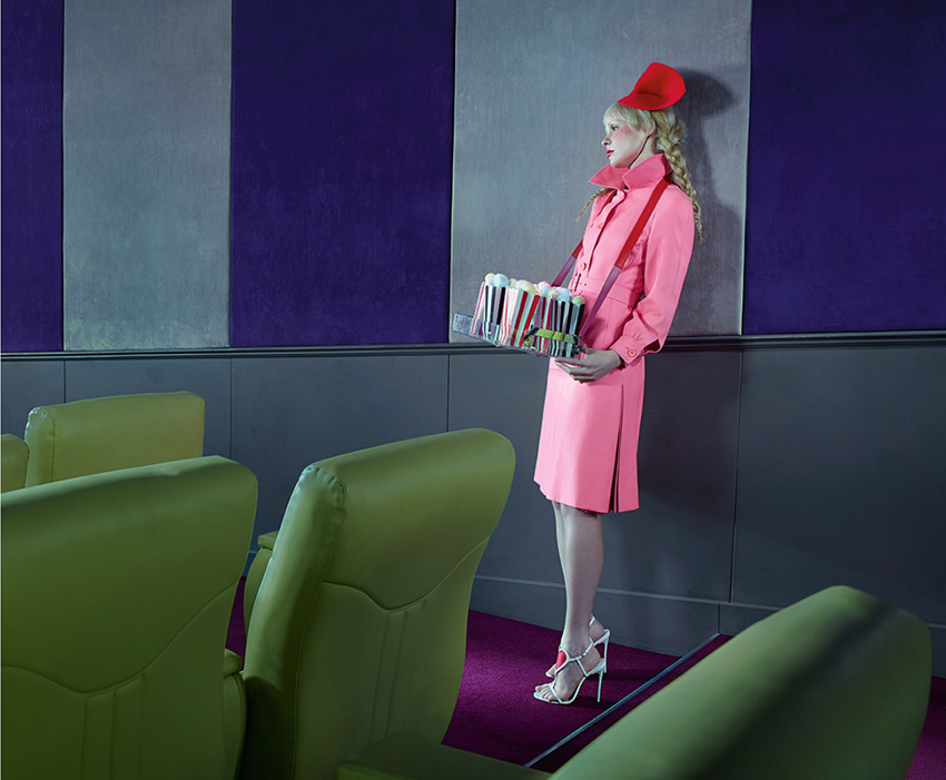Petite wears a pink coat dress from Painted Black Vintage with a red asymmetric hat by Amy Collette and heels by Christian Louboutin.