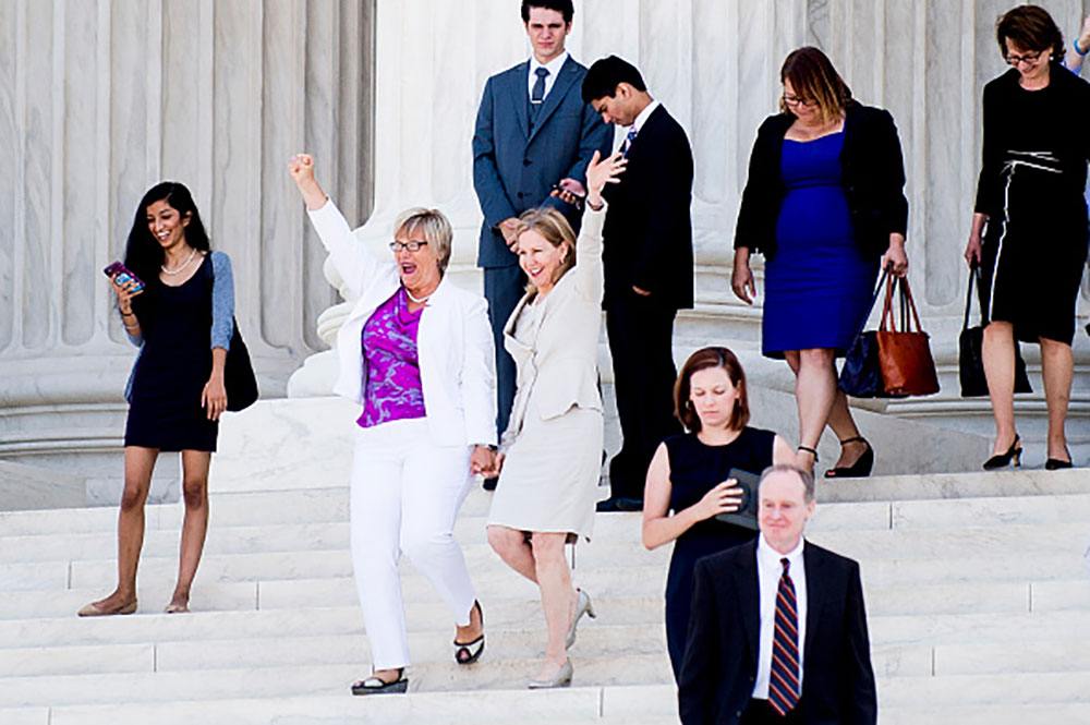 Texas abortion provider Amy Hagstrom-Miller and Nancy Northup, President of The Center for Reproductive Rights wave to supporters as they descend the steps of the Supreme Court after the ruling agains HB2. Image courtesy of Getty.