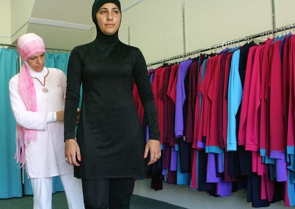 "Sydney, AUSTRALIA:  Muslim fashion designer Aheda Zanetti (L) makes adjustments to her Islamic swimsuit worn by Australian model Mecca Laalaa (R) at her shop in Sydney, 12 January 2007. The new ""Burqini"" is marketed as the first two-piece Muslim swimwear for women and is attracting customers from North America, Europe and across the Middle East.  AFP PHOTO/Anoek DE GROOT  (Photo credit should read ANOEK DE GROOT/AFP/Getty Images)"