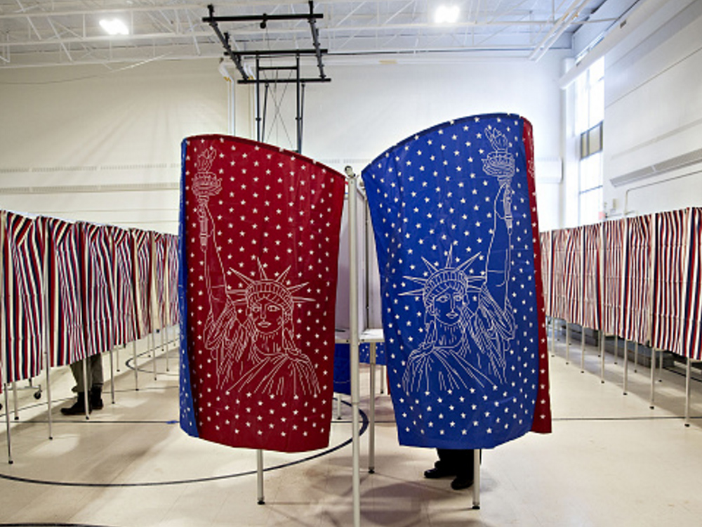 Voting booths in New Hampshire. Image courtesy of Bloomberg/Getty. View original here: http://www.gettyimages.com/license/509162338